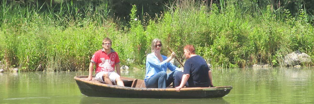 Drei Personen in einem kleinen Ruderboot