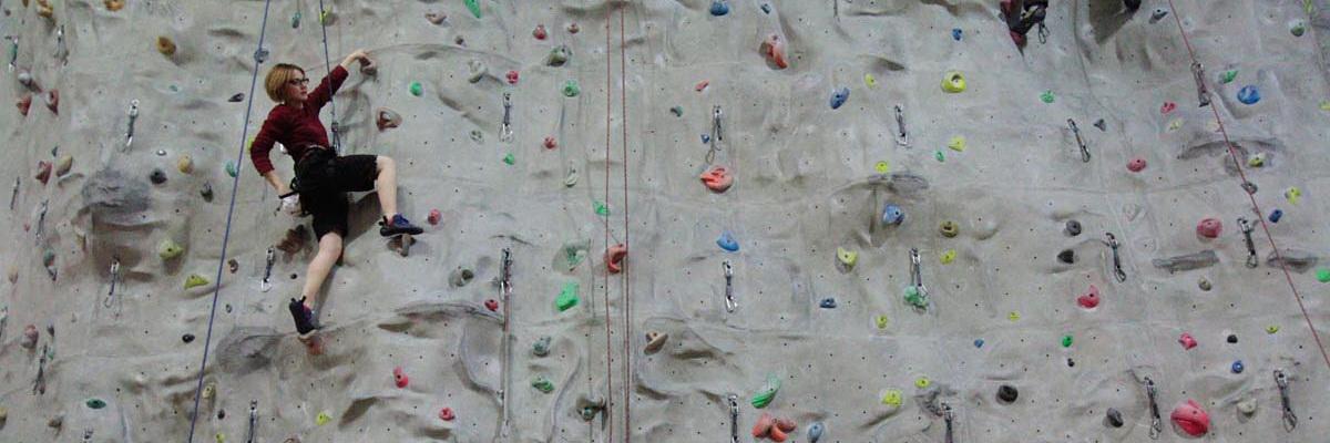 Junge Frau auf einer Kletterwand